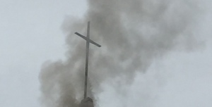 Tested by fire, the cross remains, symbolizing our commitment to peace and justice for all.